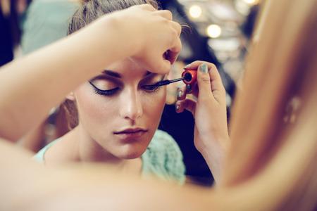 Make-up artist applying the mascara to model. Close up.