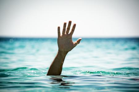 Foto de Single hand of drowning man in sea asking for help - Imagen libre de derechos