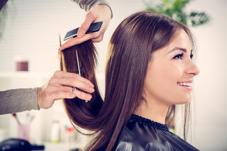 Photo pour Young beautiful woman having her hair cut at the hairdresser's. - image libre de droit
