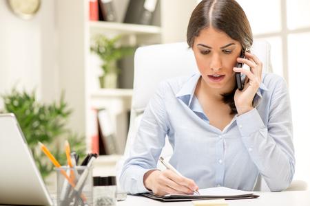 Foto de A young thinking businesswoman phoning with smart phone in office. - Imagen libre de derechos