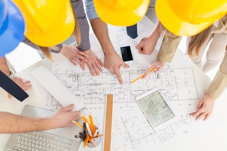 Photo pour Top view of four successful architect checking the architectural plans. - image libre de droit