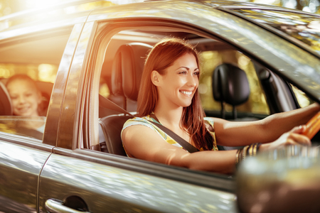 Photo for Young beautiful smiling woman driving a car.  Her cute daughter sitting on rear and enjoying. - Royalty Free Image