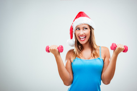 Photo for Happy fitness woman with a Santa's cap on her head, lifting dumbbells and smiling cheerful, fresh and energetic. White background. - Royalty Free Image
