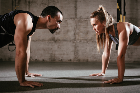 Photo for Young muscular couple doing push-up exercise at the cross fit workout. - Royalty Free Image