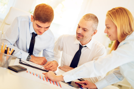 Photo pour Business people having a meeting. Three business people looking at document and discussing in the office. - image libre de droit