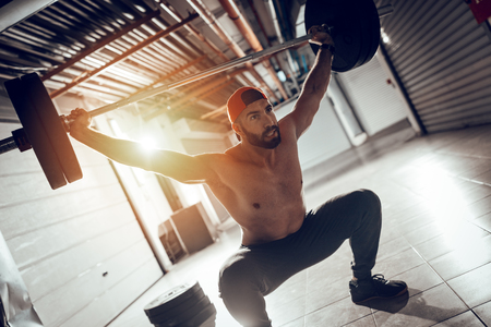 Photo for Young muscular man doing overhead squat exercise with barbell on cross training at the garage gym. - Royalty Free Image
