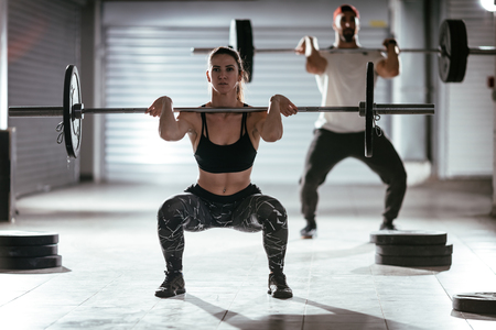 Photo pour Young muscular couple doing a high pull exercise with barbell on cross training at the garage gym. - image libre de droit