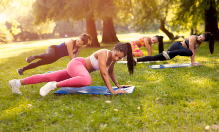 Photo for Four beautiful female friends doing exercise in the park.  - Royalty Free Image