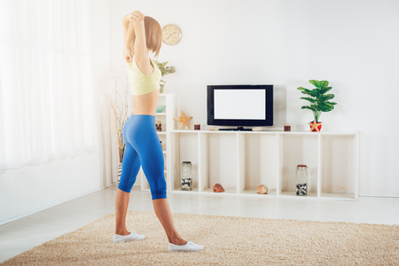 Photo pour Fit woman warming up while doing stretching exercises at home in front of TV. - image libre de droit