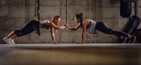 Photo for Two young muscular girls doing plank exercise at the cross fit workout. - Royalty Free Image