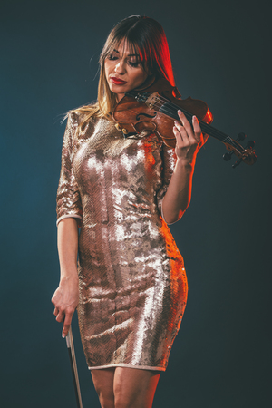 Photo for Beautiful young smiling woman in sequin dress playing the classical music on violin. - Royalty Free Image