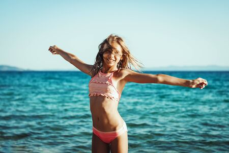 Photo pour Cute teenager girl having fun on the beach and grabs the last rays of the sunset sun. - image libre de droit