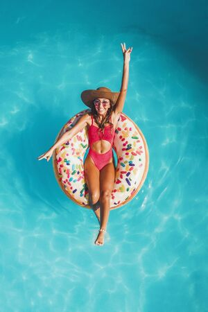 Foto für Top view of a beautiful young woman in swimming pool swims on inflatable ring donut and has fun on vacation. - Lizenzfreies Bild