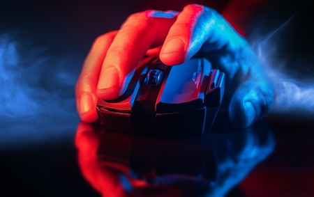 Foto de Close up of Hand over wireless Game Mouse on dark background and smoke ; The finger ready to click - Imagen libre de derechos