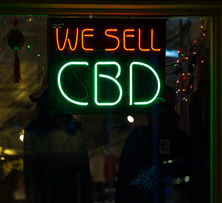 Photo pour ASHEVILLE, NC, USA-2/16/19: A store advertises cannabidiol with red and green neon signs. - image libre de droit