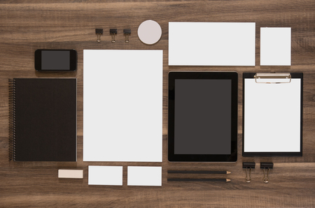 Foto de Set of mock-up business brand template on wooden desk. Set of stationery with black notepads and tablet. Mobile phone. - Imagen libre de derechos