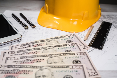 Photo pour Construction industry costs money us dollars banknotes by tools safety equipment and blueprints - image libre de droit