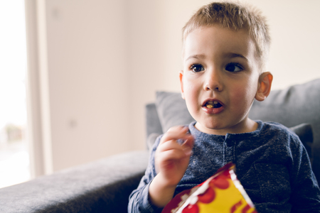 Photo for Portrait of a little small boy eating unhealthy snacks corn peanut flips at home - Royalty Free Image