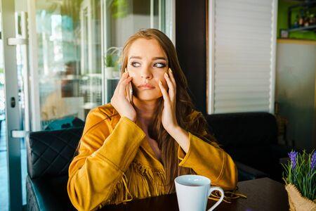 Foto de Portrait of young beautiful woman at cafe restaurant talking to the mobile phone call receiving disturbing surprising news face reacting - Imagen libre de derechos