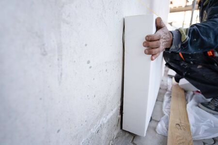 Photo pour Worker placing  sheet insulation to the wall at construction site Rigid extruded polystyrene insulation board for energy saving Of Facade house renovation energy efficient - image libre de droit