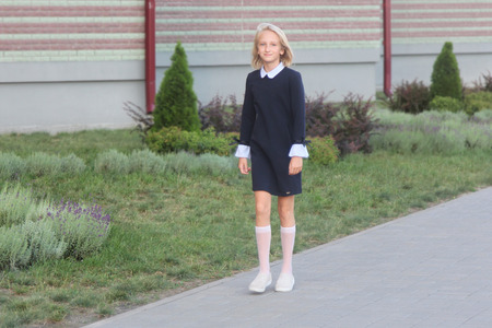 Photo pour Beautiful blonde girl in elegant dress goes to school. Back to school. - image libre de droit