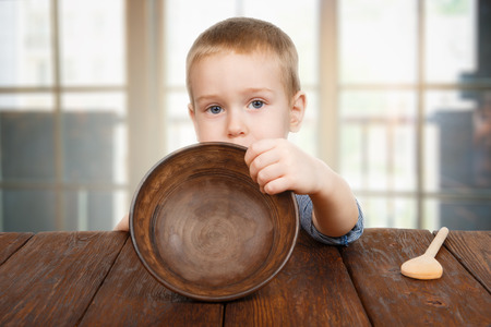 Photo for Cute small child boy sitting at wooden table shows empty plate - Royalty Free Image