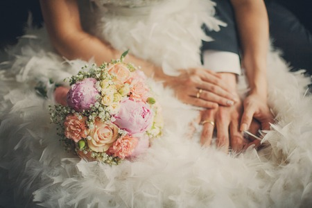 Foto de Wedding pastel bouquet closeup in front of couple - groom and bride's hands with elegant manicure. Bouquet lays on the dress with swan feather decor - Imagen libre de derechos