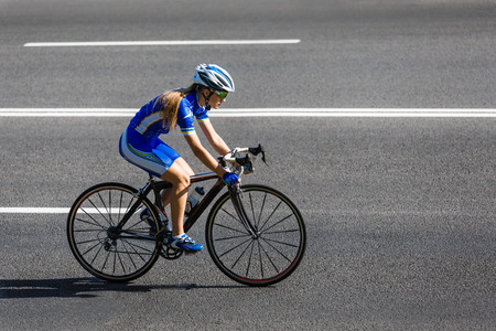 Foto de Female sportsman cyclist riding racing bicycle. Woman cycling on countryside road or highway. Training for triathlon or cycling competition. - Imagen libre de derechos
