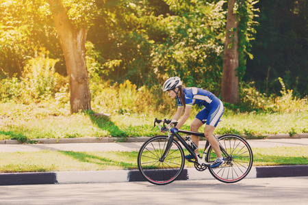 Foto de Female sportsman cyclist riding racing bicycle. Woman cycling on countryside summer sunny road or highway. Training for triathlon or cycling competition. - Imagen libre de derechos