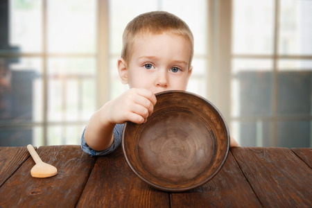 Foto de Child hunger concept. Small toddler boy shows empty bowl sitting at dark wood table with wooden spoon. Cute child has no food in plate - Imagen libre de derechos