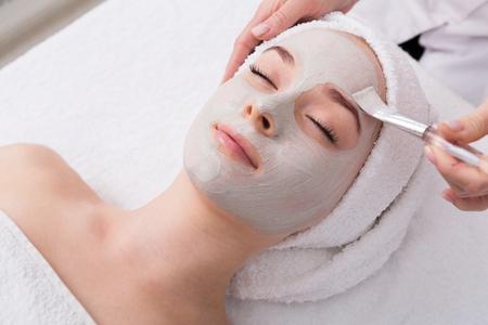 Photo pour Face peeling mask, spa beauty treatment, skincare. Woman getting facial care by beautician at spa salon, side view, close-up - image libre de droit
