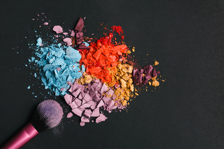 Beauty, makeup cosmetics. Eyeshadow splash palette and brush, colorful crushed eye shadow powder, flat lay, top view, black background