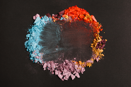 Beauty, makeup cosmetics. Eyeshadow splash palette, colorful crushed eye shadow powder, flat lay, top view, black background, shallow depth of field
