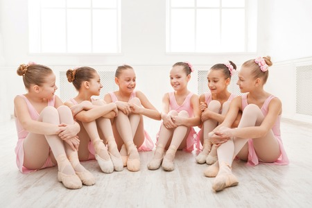 Photo pour Little ballerinas talking in ballet studio. Group of girls having break in practice, sitting on floor. Classical dance school - image libre de droit