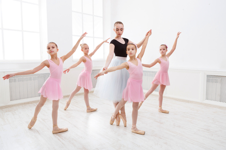Foto de Young ballet teacher and students ballerinas in dance class. Girls are engaged in choreography in the ballet school. - Imagen libre de derechos