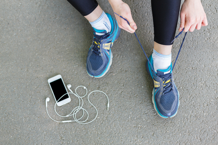 Photo pour Woman tying shoes laces before running, getting ready for jogging in park, top view - image libre de droit
