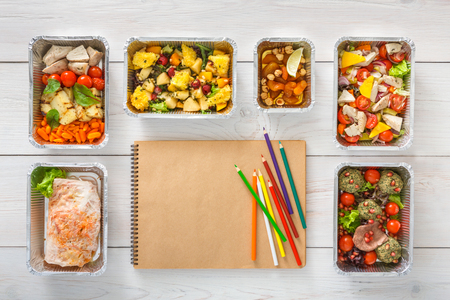 Foto de Diet plan with healthy restaurant food delivery. Natural organic fitness nutrition. Daily meals in foil boxes with copy space on craft paper notebook. Top view, flat lay - Imagen libre de derechos