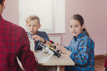 Foto de Children creating robots at school, stem education, copy space. Early development, diy, innovation, modern technology concept - Imagen libre de derechos