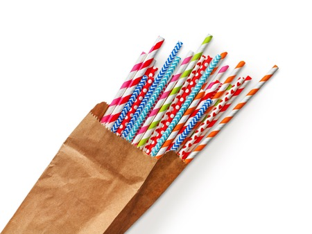 Foto de Colorful striped party cocktail straws in craft paper bag isolated on white background. Bright plastic pipes - Imagen libre de derechos