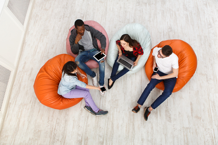 Foto de Group of young multiethnic friends using gadgets sitting indoors at university campus and working together on creative task, top view with copy space - Imagen libre de derechos