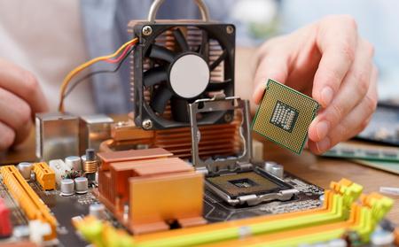 Foto de Technician plug in CPU microprocessor to motherboard close up. Computer upgrade in service center - Imagen libre de derechos