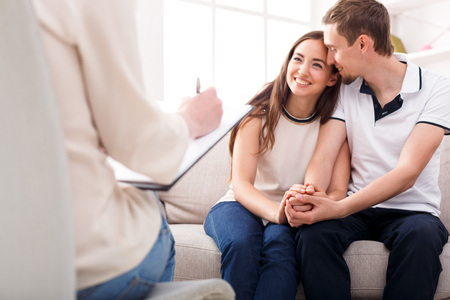 Photo for Happy couple reconciling at therapy session in psychotherapists office - Royalty Free Image