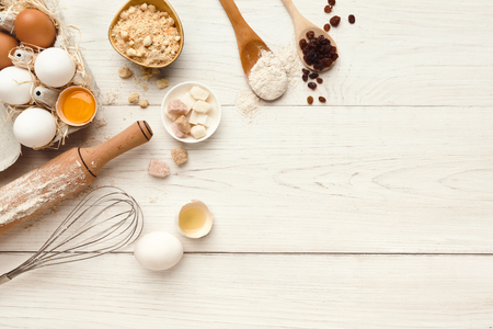 Photo for Cooking ingredients background. Border of flour, eggs, raisins, sugar and kitchen utensils on white rustic wood with copy space. Dough preparing and pastry concept, top view - Royalty Free Image
