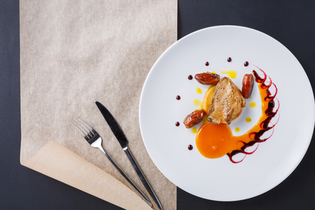 Foto de Roasted goose liver with date, apple and fruit and berry sauce painting with cutlery top view. Creative french cuisine, delicatessen restaurant meal - Imagen libre de derechos