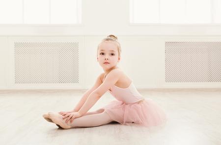 Photo pour Portrait of little ballerina on floor, copy space. Smiling baby girl dreaming to become professional ballet dancer, classical dance school - image libre de droit