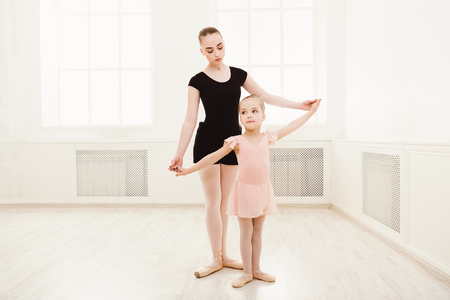 Photo for Little girl learning ballet with teacher copy space. Cute small ballerina training classical dance exercises with female coach. - Royalty Free Image