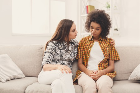 Foto de Two sad diverse women talking at home. Female friends supporting each other. Problems, friendship and care concept - Imagen libre de derechos