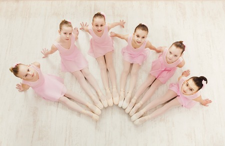 Photo for Little ballerinas in ballet studio, top view. Group of girls practicing position sitting on floor, classical dance studio - Royalty Free Image