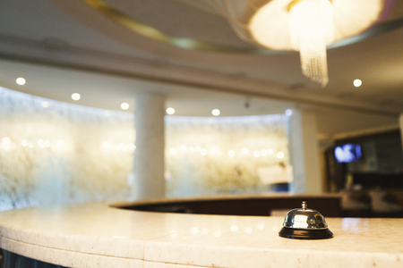 Photo pour Hotel accommodation call bell on reception desk, contemporary interior, copy space - image libre de droit