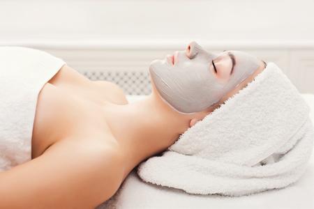 Photo pour Face mask, spa beauty treatment. Woman applying facial clay mask at spa salon, skincare, top view, overhead - image libre de droit